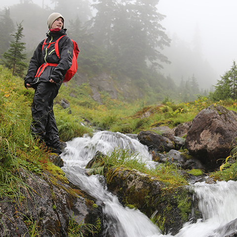 Hiker overlooking mountain stream