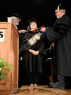 Teri Rofkar stands barefoot on the stage at Allen Hall, to receive her Doctor of Fine Arts degree.